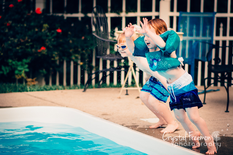 two boys jumping into pool