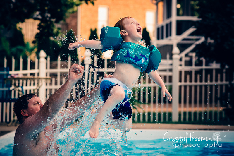 Four year old boy being thrown into pool