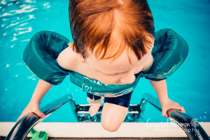 Four year old red headed boy climbing out of pool.
