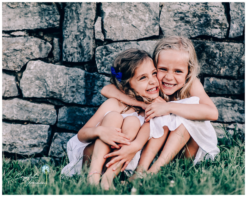 Giggly sisters hugging in front of stone rocks.