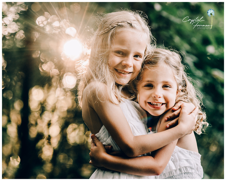 Four-year old and six-year old sisters hugging with beautiful sunlight behind them at Winstead Park in Franklin, TN